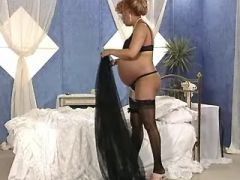 Ethnic pregnant chick in stockings caress paunch