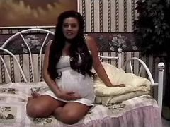 Lonely round pregnant girl relaxes in bedroom